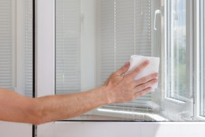 Houseworker cleans window