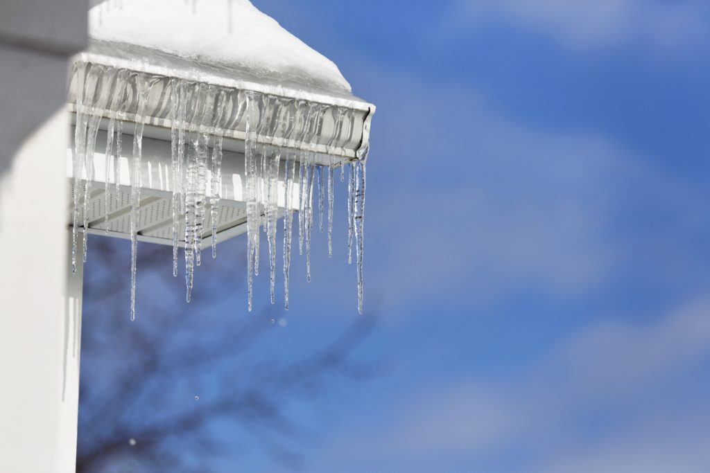 Icicles Melting Over Roof Edge Gutter